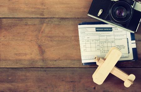 imagen: tapa de la vista de volar boleto de avión de madera y cámara de la vendimia sobre la mesa de madera. retro imagen filtrada