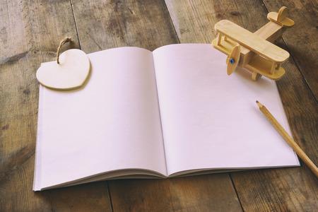 papel de notas: cuaderno en blanco abierto sobre la mesa de madera. listo para la maqueta. retro imagen filtrada Foto de archivo
