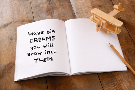 failure: open notebook with Inspirational motivating quote next to wooden airplane, over wooden table