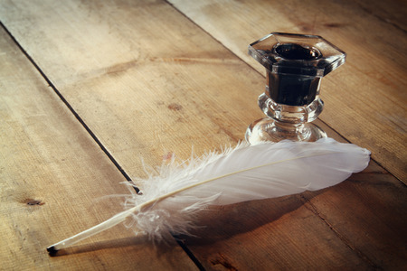 inkstand: photo of white Feather and inkwell on old wooden table. retro filtered image