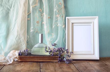grabado antiguo: nueva botella de perfume de la vendimia lado de las flores aromáticas y antiguo marco en blanco en la mesa de madera. retro imagen filtrada