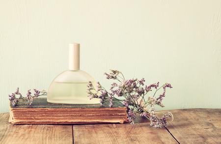 木製のテーブルに香りのよい花の横に新鮮なビンテージ香水瓶。レトロなフィルター処理されたイメージ