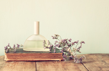 fragrance: fresh vintage perfume bottle next to aromatic flowers on wooden table. retro filtered image Stock Photo