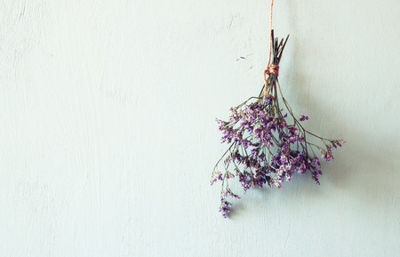 wild life: bouquet of dried flowers hanging on rope against wooden background