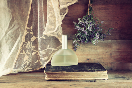 fragrant scents: fresh vintage perfume bottle next to aromatic flowers on wooden table. retro filtered image Stock Photo