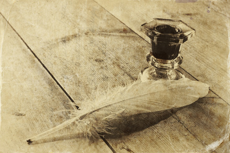 inkwell: photo of white Feather and inkwell on old wooden table. retro filtered image, black and white style photo