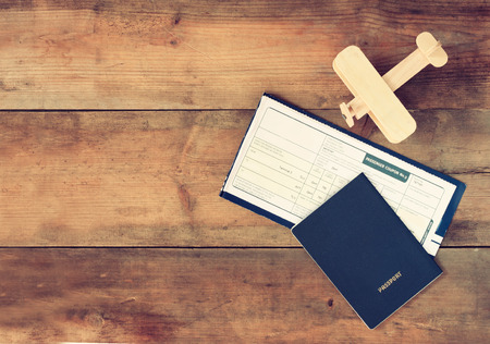 plane table: top view image of flying ticket wooden airplane and passport over wooden table