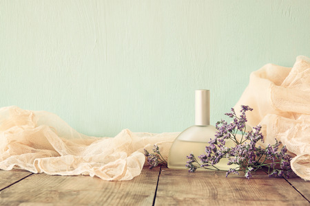 dressing up: fresh vintage perfume bottle next to aromatic flowers on wooden table. retro filtered image Stock Photo