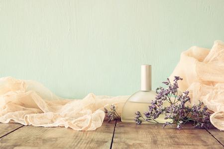 vistiendose: nueva botella de perfume de la vendimia lado de las flores aromáticas en la mesa de madera. retro imagen filtrada