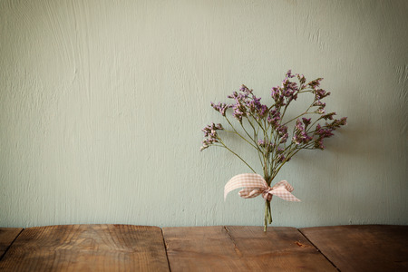 flower arrangement: bouquet of dried flowers rope against wooden background