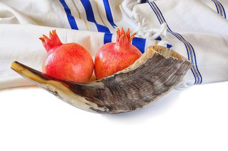 yom: shofar horn, white prayer talit and pomegranate isolated on white. rosh hashanah jewish holiday concept . traditional holiday symbol. Stock Photo
