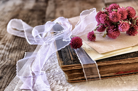 writing desk: selective focus image of dry flowers and old vintage books on wooden table. retro filtered image Stock Photo