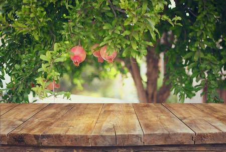 vintage wooden board table in front of dreamy pomegranate tree landscape. retro filtered image Foto de archivo