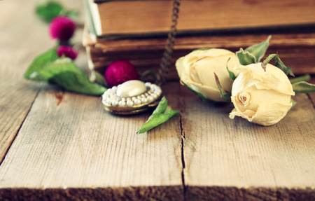 jewelry background: selective focus image of dry rose, antique necklace and old vintage books on wooden table. retro filtered image Stock Photo