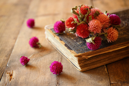 antique books: selective focus image of dry flowers, antique necklace and old vintage books on wooden table. retro filtered image