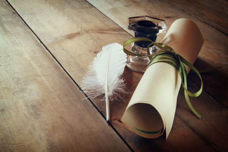 scroll: photo of white Feather, inkwell and scroll paper on old wooden table. retro filtered image