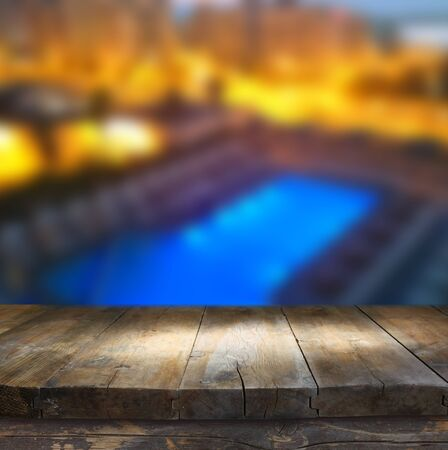 night table: wood board table in front of rich hotel pool at night. Ready for product display montages
