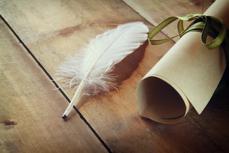 piuma bianca: Foto di piuma bianca e rotolo di carta sul vecchio tavolo di legno. immagine filtrata retrò Archivio Fotografico