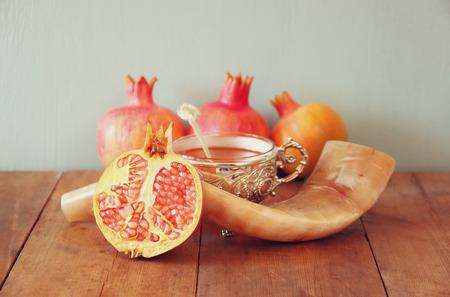 shofar: rosh hashanah jewesh holiday concept - shofar, honey, apple and pomegranate over wooden table Stock Photo