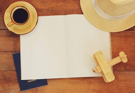 aeroplane: top view image of open notebook with blank pages, cup of coffee wicker hat and wooden aeroplane over wooden table. ready for mockup or adding text. travel concept