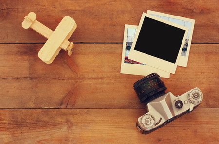 family vacation: top view image of old blank instant photo, wood aeroplane and old camera over wooden table Stock Photo