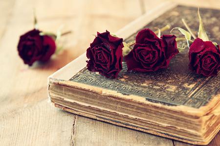 ロマンス: 乾燥の赤いバラと木製のテーブル上の古いビンテージ本のセレクティブ フォーカス画像。レトロなフィルター処理されたイメージ