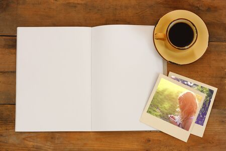 notebooks: top view of open blank notebook and photographs next to cup of coffee over wooden table Stock Photo