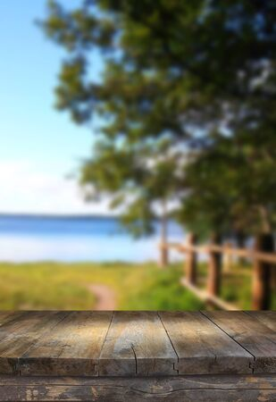 forest products: vintage wooden board table in front of dreamy and abstract forest lake landscape with lens flare.