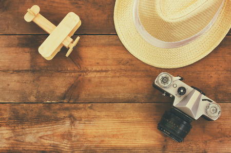 aeroplane: top view image of wood aeroplane, fedora hat and old camera over wooden table