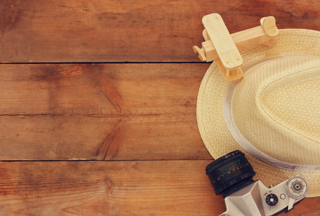 fedora: top view image of wood aeroplane, fedora hat and old camera over wooden table