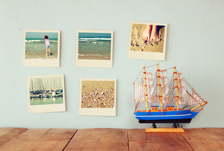 album: instant photos hang over wooden textured background next to decorative boat. retro filtered image