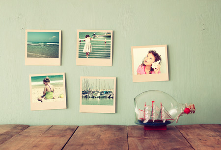 memories: instant photos hang over wooden textured background next to decorative boat in the bottle. retro filtered image