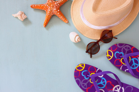 fedora: colorful flip flops, starfish, shells, fedora hat and sunglasses on wooden background