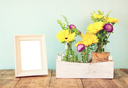 photo frame: summer bouquet of flowers next to blank vintage photography frame on the wooden table with mint background. vintage filtered image