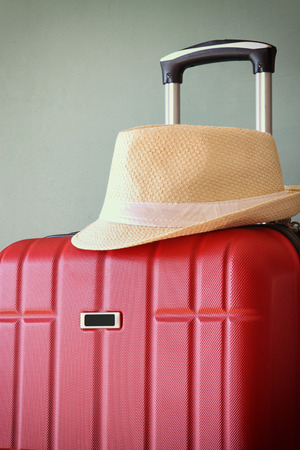 exclusive photo: image of red elegant travel luggage and fedora hat in front of sea. travel and vacation concept