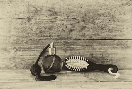 cosmetics background: photo of vintage perfume bottle next to old wooden hairbrush on wooden table. black and white old style photo