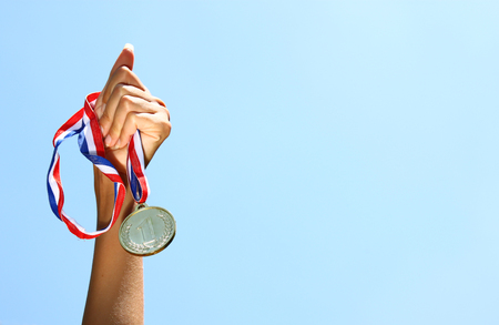 woman hand raised, holding gold medal against skyl. award and victory concept. selective focus. retro style image. Stock Photo