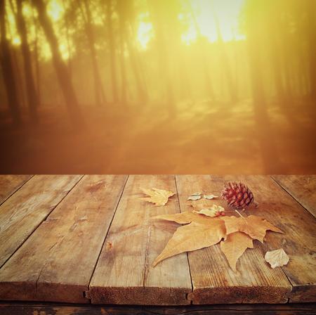 trompo de madera: Fondo de otoño de las hojas caídas sobre la mesa de madera y backgrond bosque con reflejo en la lente y el atardecer Foto de archivo