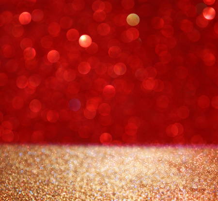red glittery: abstract background of red and gold glitter bokeh lights, defocused.