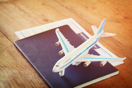aeroplane: toy airplane and passport over wooden table. retro style image