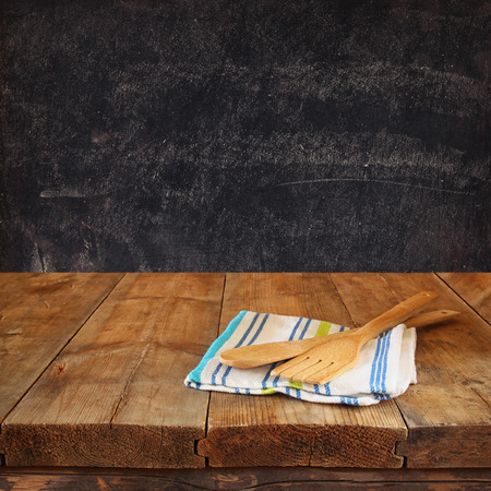 cooking utensil: Kitchen utensils on tablecloth on wooden textures table against chalkboard background