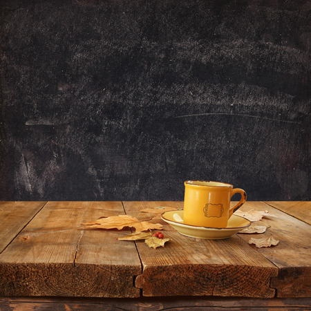 chalk board: front image of coffee cup over wooden table and autumn leaves in front  and blackboard backgrond with room for text