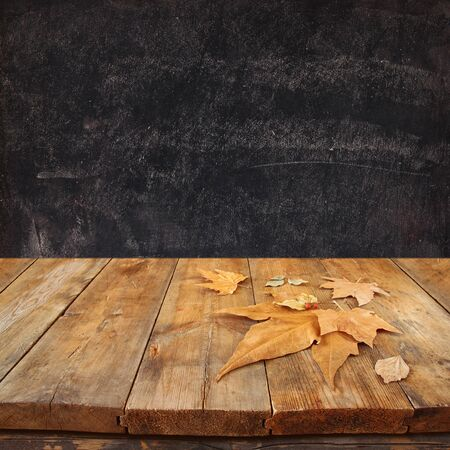 vintage photo: autumn background of fallen leaves over wooden table and blackboard backgrond with room for text Stock Photo