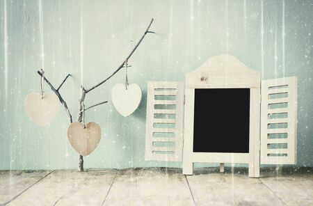 new filter: decorative chalkboard frame and wooden hanging hearts over wooden table. ready for text or mockup. retro filtered image with glitter overlay