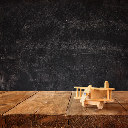 kids toys: image of wooden toy airplane over wooden table against chalk blackboard background. retro style image Stock Photo