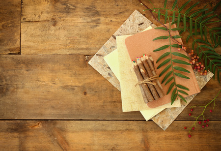 paper stack: vintage notebook, old paper and stack of colorful wooden pencils over wooden table