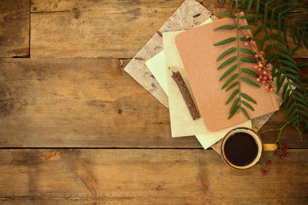 vintage notebook, old paper and wooden pencil next to cup of coffee over wooden table Stock Photo