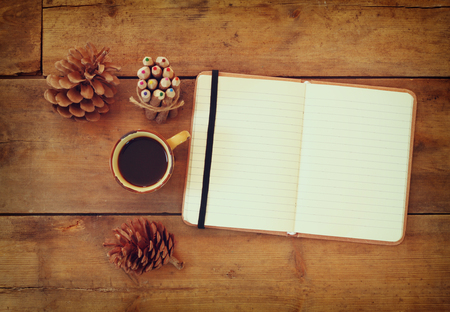 writing desk: top image of open notebook with blank pages, next to pine cones and cup of coffee over wooden table