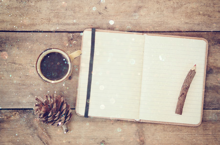 top image of open notebook with blank pages, next to pine cones and cup of coffee over wooden table. top image, glitter overly
