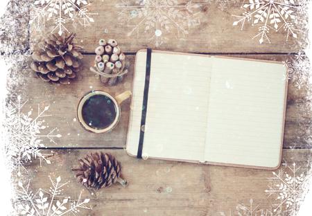 hacer: la parte superior de la imagen cuaderno abierto con páginas en blanco, junto a los conos de pino y una taza de café sobre la mesa de madera. la parte superior de imagen, brillo excesivamente con copos de nieve Foto de archivo